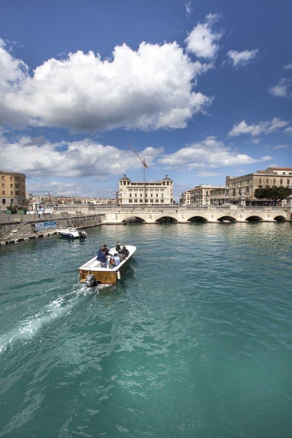Syracuse, Italia Un barco cruza el canal en la ciudad imagen de archivo libre de regalías