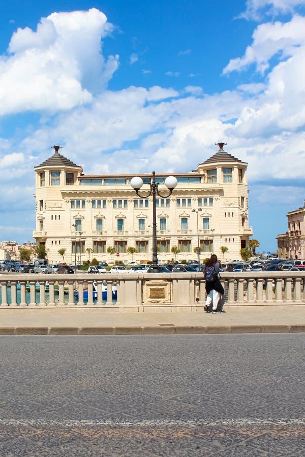 Syracuse Sicilien, Italien - April 10th 2019: Manligt turist- fotografanseende på bron och tabild av den härliga hamnen royaltyfri foto