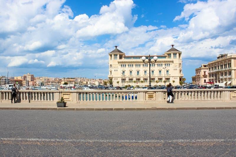 Syracuse Sicilien, Italien - April 10th 2019: Turister som står på en bro och tar bilder av en härlig marina på en solig dag fotografering för bildbyråer