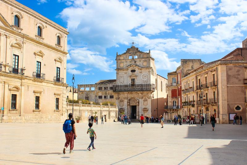 Syracuse, Sicily, Italy - Apr 10th 2019: Historical Piazza Duomo Square in Ortygia Island photographed with tourists on a sunny. Day. Santa Lucia Church in stock image