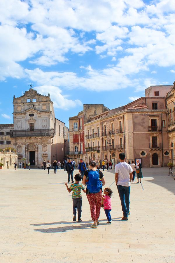 Syracuse, Sicily, Italy - Apr 10th 2019: Sightseeing people on the Piazza Duomo Square in Ortigia Island. Amazing Santa Lucia Alla. Badia Church in background stock images