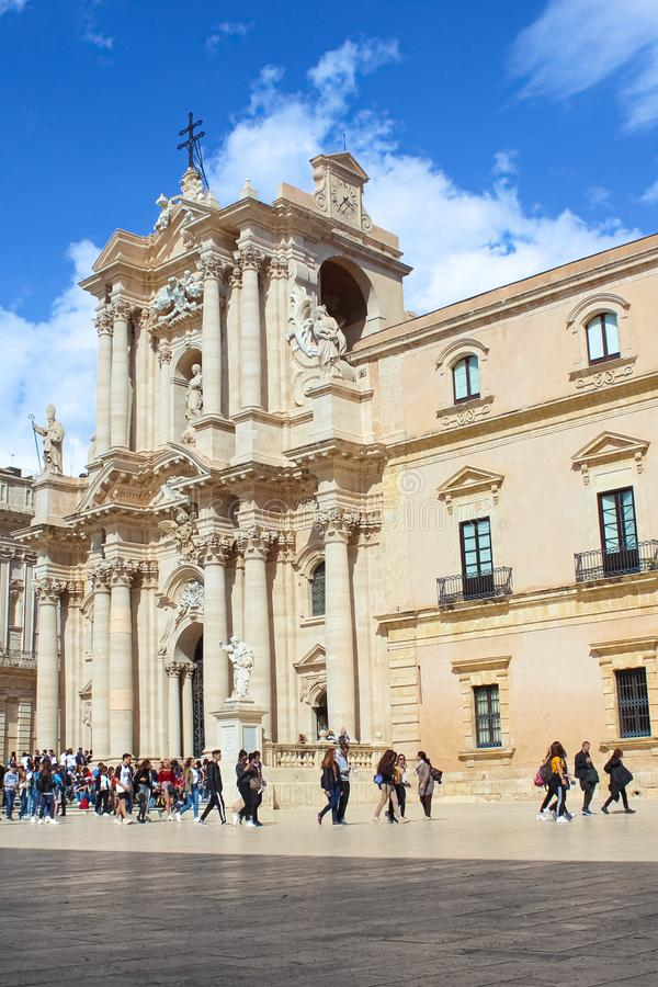 Syracuse, Sicily, Italy - Apr 10th 2019: Tourists in front of beautiful Syracuse Cathedral on Piazza Duomo Square in Ortygia. Island. Piece of Baroque stock image