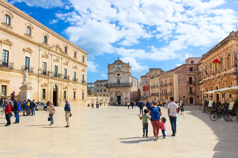 Syracuse, Sicily, Italy - Apr 10th 2019: Tourists walking on the Piazza Duomo Square. Beautiful Santa Lucia Alla Badia Church. In background. Sunny day. Popular stock image