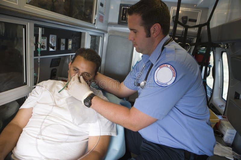 Syremaskering för doktor Helping Man With fotografering för bildbyråer