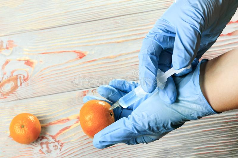 The syringe is in mandarin. in the syringe is blue liquid. Mandarin is in the hands of a man, and he controls the injection of. Mandarin. there is toning stock image