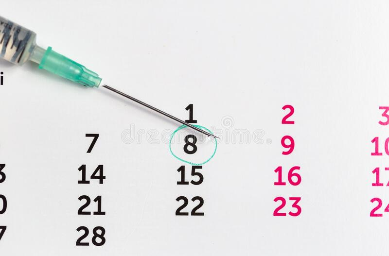 Syringe with vaccine drop over a calendar. Remember to get your vaccine, injection, fertility concept stock images