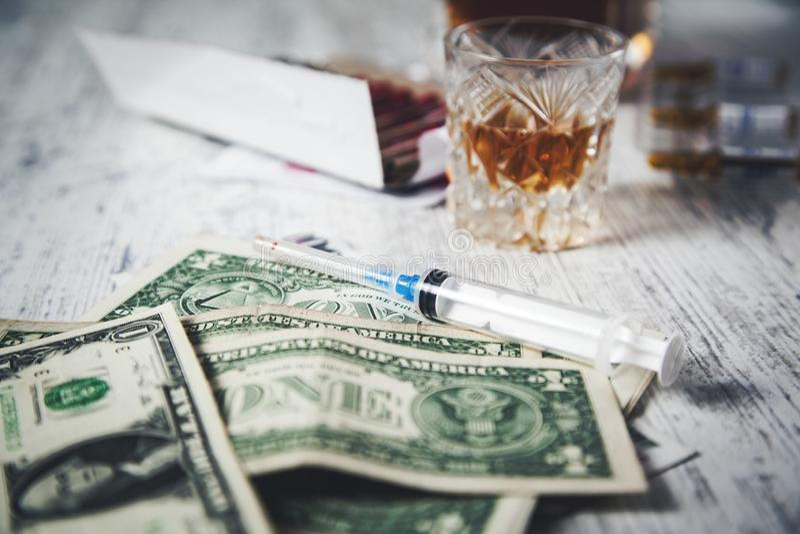 Syringe and whiskey and money. Money with syringe and whiskey  on the desk royalty free stock photos