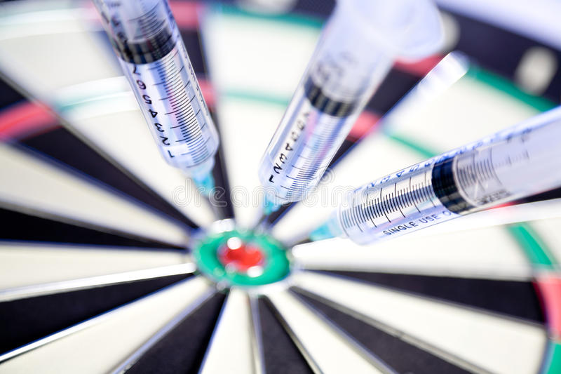 Syringes Stuck In A Dartboard Stock Photos