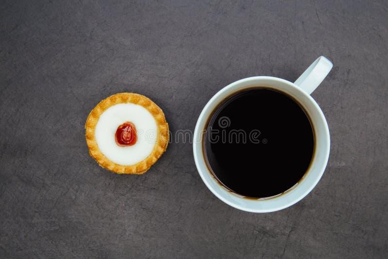 Syrlig kaka för körsbärsröd bakewell och kaffekopp royaltyfri foto