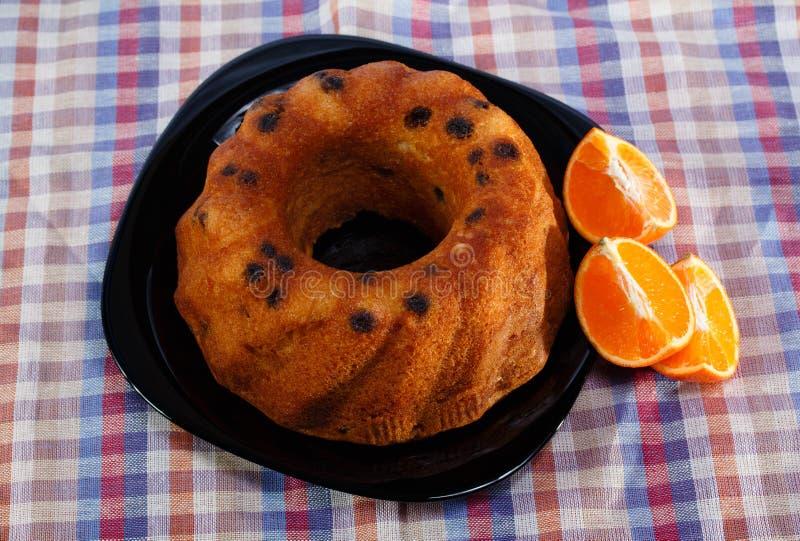 Syrligt med ny orange toppning i svart maträtt royaltyfria foton