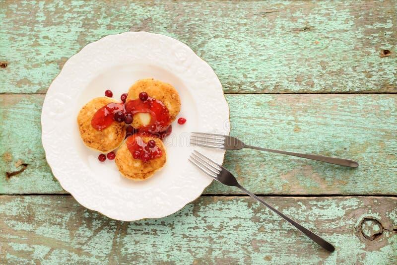 Syrniki, ρωσικές τηγανίτες τυριών εξοχικών σπιτιών με τη μαρμελάδα σμέουρων για στοκ εικόνες