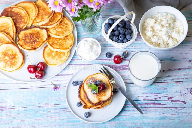 Syrniki de cr?pes de fromage blanc Gâteaux au fromage faits maison du fromage blanc avec la crème sure, les baies et le lait photo libre de droits