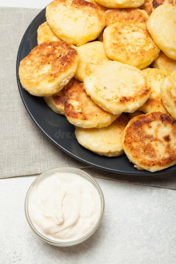 Syrniki frit fait maison de fromage avec la crème sure images libres de droits