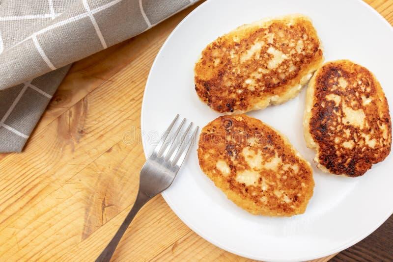 Syrniki ou sirniki russe, beignets faits maison de fromage blanc ou crêpes petit déjeuner avec des pankakes de lait caillé, vue s photographie stock libre de droits