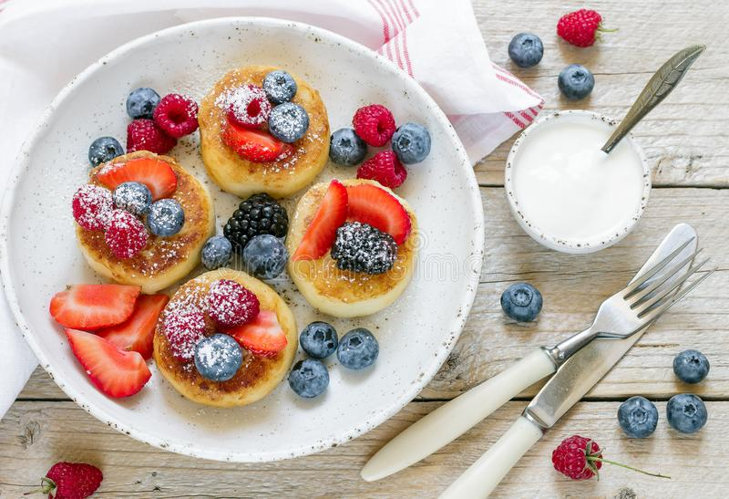 Syrniki Pancake della ricotta, syrniki, frittelle della cagliata con le bacche fresche immagini stock libere da diritti