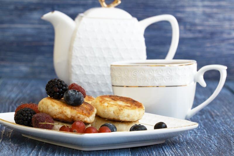 Syrniki russe, sirniki, beignets de fromage blanc ou crêpes servis avec la baie, théière blanche de porcelaine et tasse de thé de image libre de droits