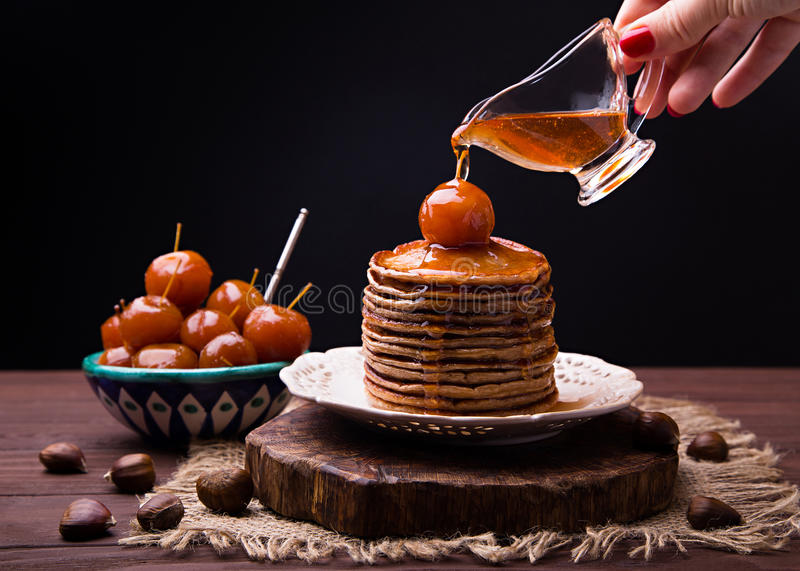 Syrup from Chinese apples jam pouring on stack of chestnut pancakes royalty free stock image