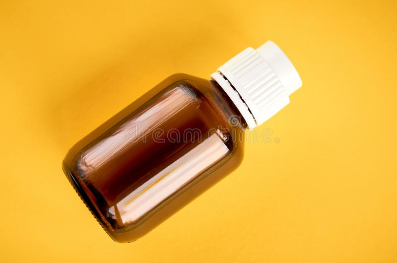 Syrup in glass bottle composition on yellow background. Flat lay and top view photo medicine cough health medical care illness liquid flu healthcare cold sick royalty free stock images