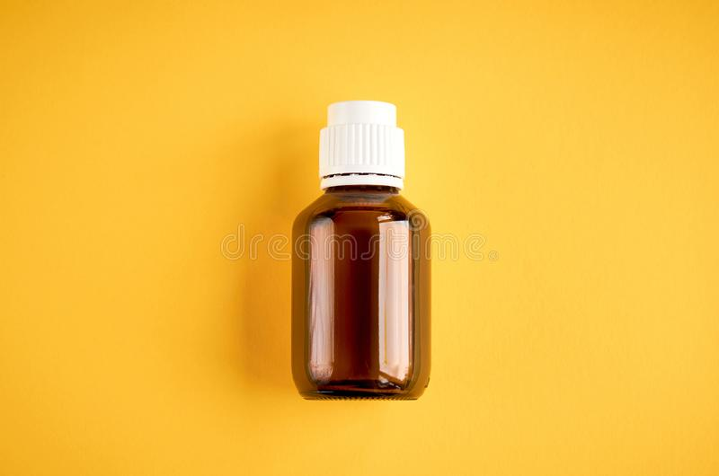 Syrup in glass bottle composition on yellow background. Flat lay and top view photo medicine cough health medical care illness liquid flu healthcare cold sick stock image