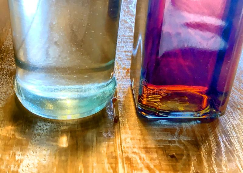 Glass bottles containing clear and brown liquids on wood table. Syrup in a glass bottles on a wood grain table stock photos