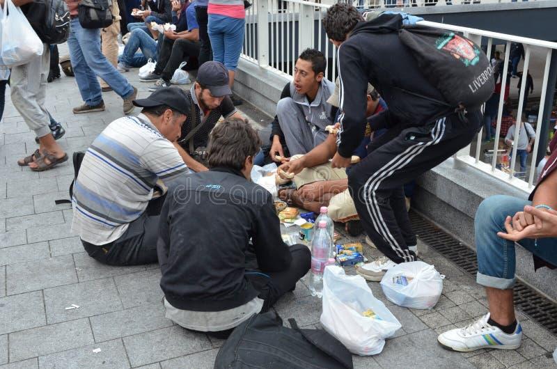 Syryjscy wędrownicy karmią na ziemi blisko Budapest międzynarodowej staci kolejowej obrazy royalty free