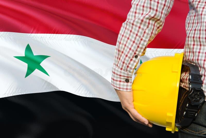 Syryjski inżynier trzyma żółtego zbawczego hełm z machać Syrii chorągwianego tło Budowy i budynku poj?cie obraz stock