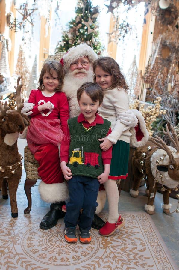 3 syskon, 2 flickor och 1 pojkesammanträde på jultomten med det dekorerade trädet i bakgrund arkivfoton