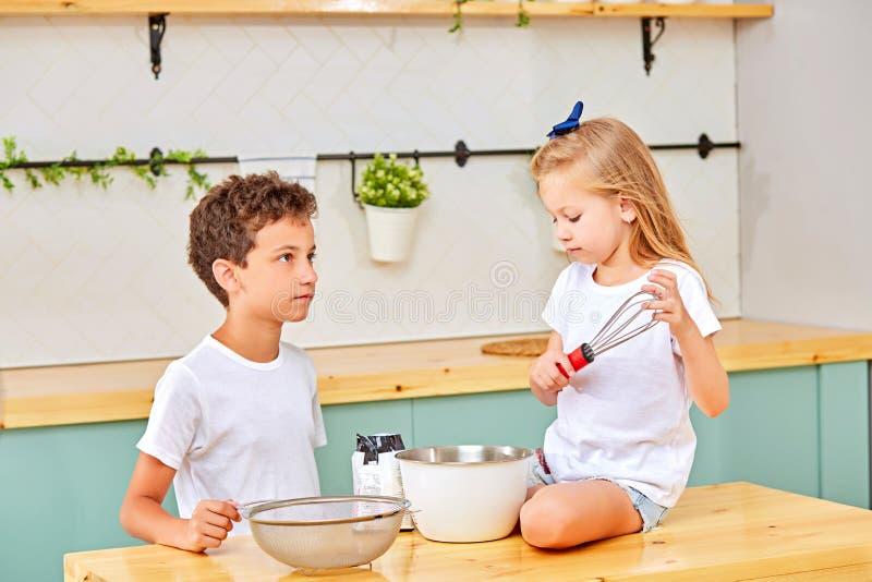 Syskon som blandar deg för bakelse i kök arkivbilder