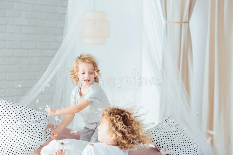 Syskon som har kuddekamp royaltyfri foto