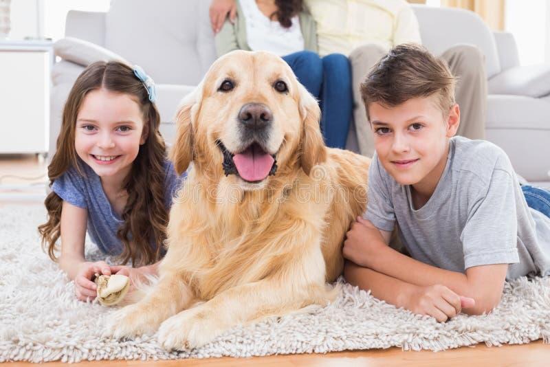 Syskon som ligger med hunden medan föräldrar som kopplar av på soffan royaltyfria bilder