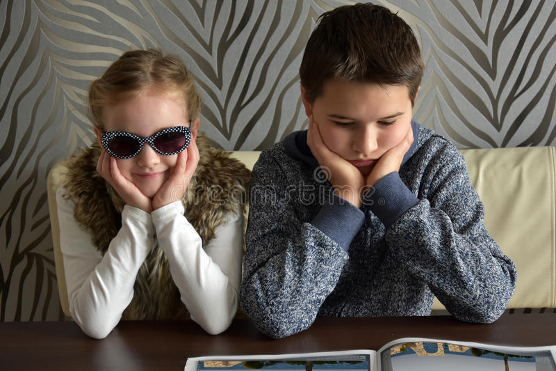 Syskon som ser boken royaltyfri bild