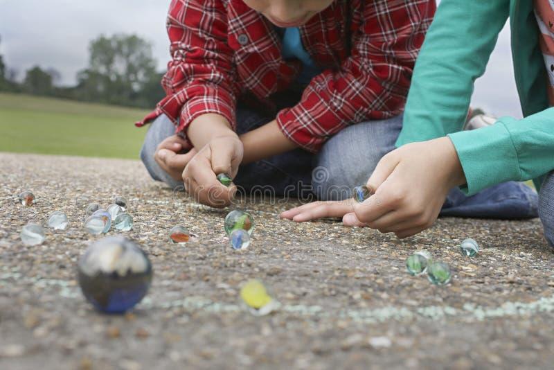 Syskon som spelar marmor på lekplats royaltyfri foto