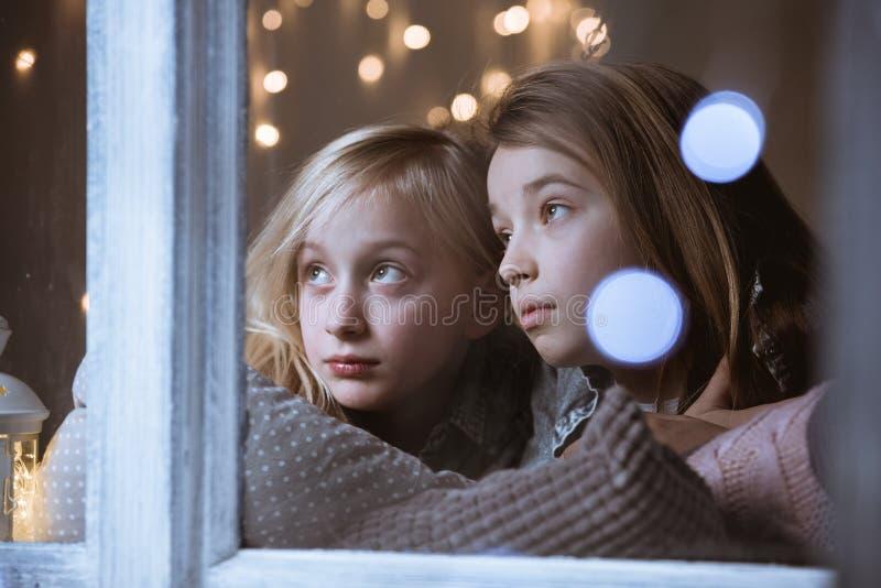 Syskon som ut ser fönstret arkivfoto