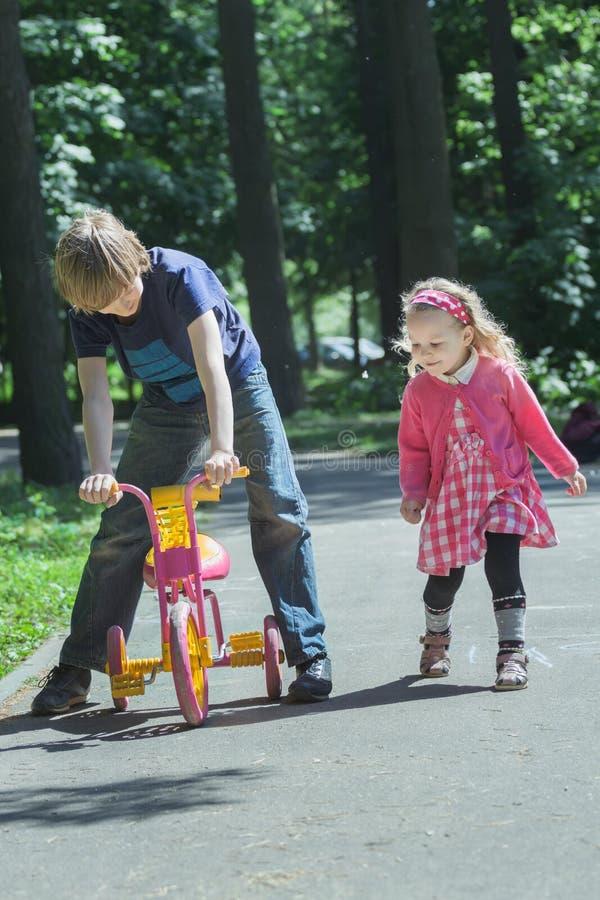 Syskonet som spelar med rosa färg- och gulingungetrehjulingen parkerar på, grov asfaltbeläggningvandringsledet royaltyfri fotografi