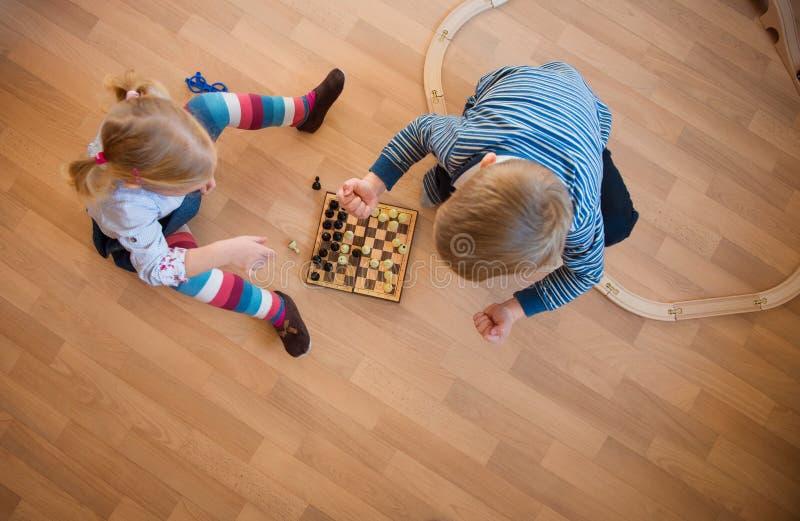Syskongrupp som spelar med schack royaltyfria bilder