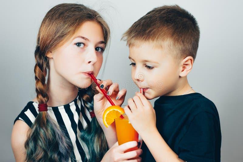 Syskongruppdrinkfruktsaft till och med sugrör från det samma exponeringsglaset royaltyfri fotografi