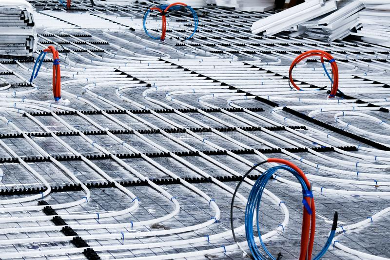 Système de chauffage par le sol avec les tuyaux blancs pendant la construction photographie stock