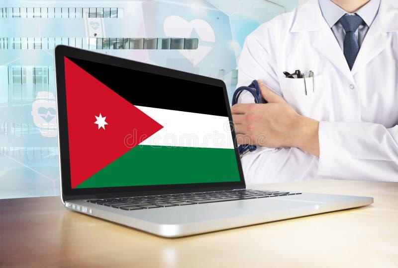 Système de santé de la Jordanie dans le thème de technologie Drapeau jordanien sur l'écran d'ordinateur Docteur se tenant avec le photos libres de droits