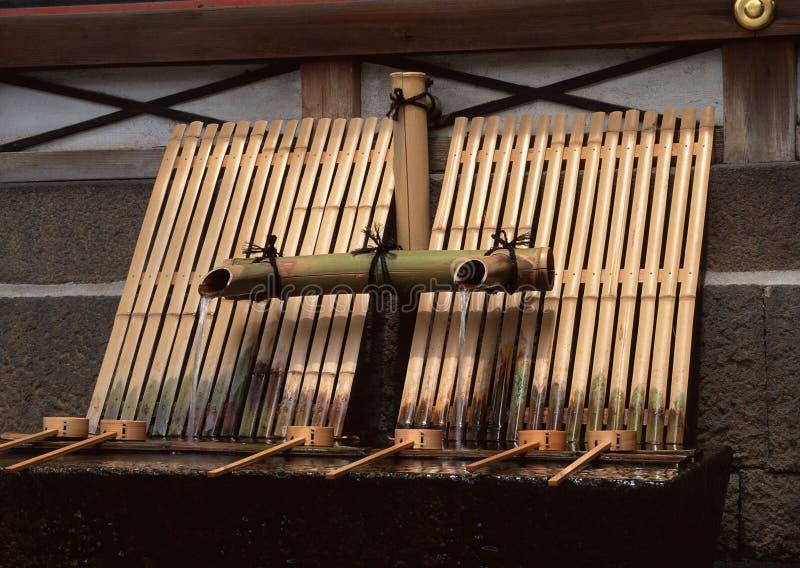 Système en bambou japonais d'eau potable avec le fond débordant de l'eau images libres de droits