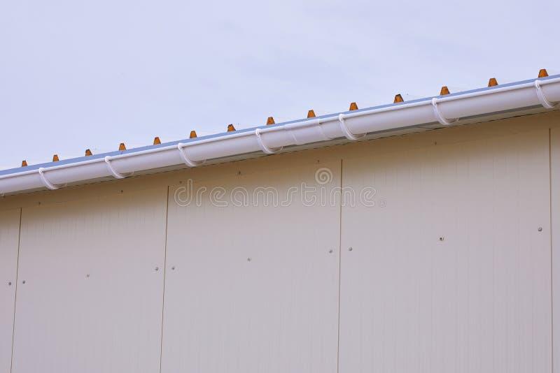 Système en plastique blanc de gouttières de pluie Ext?rieur de tuyau de drainage de goutti?res photographie stock libre de droits