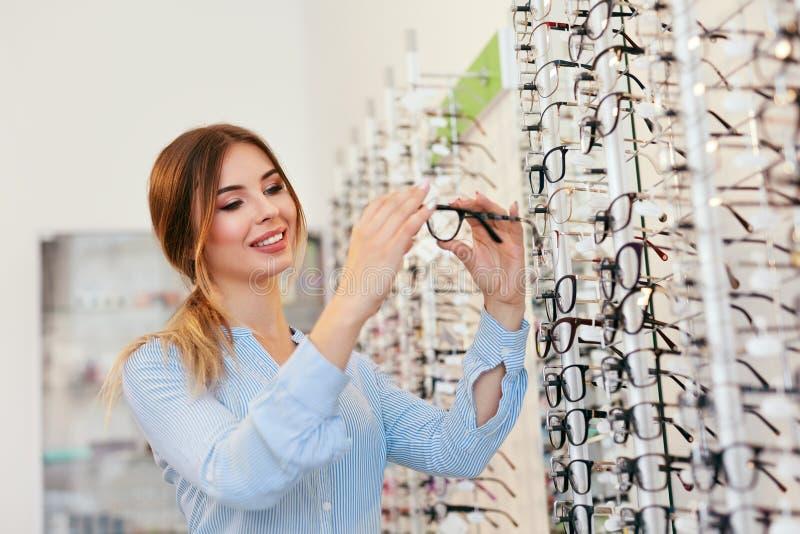 Système optique Femme près de l'étalage recherchant des lunettes images libres de droits