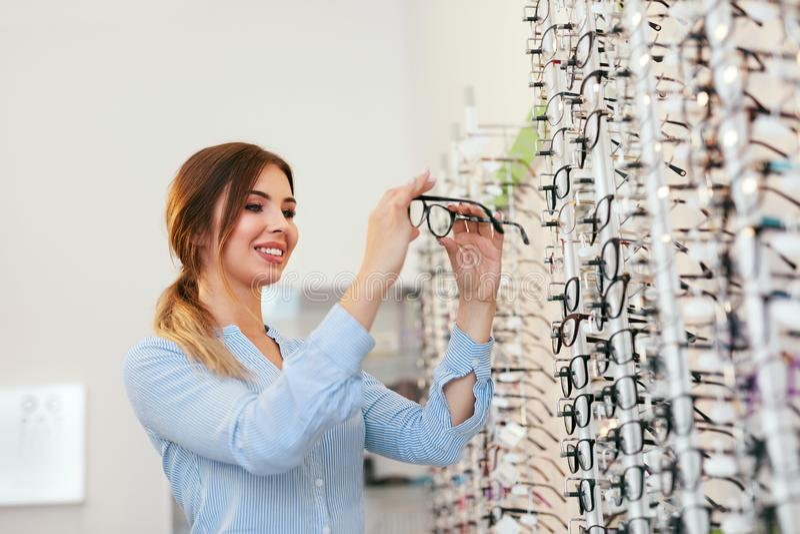 Système optique Femme près de l'étalage recherchant des lunettes photo libre de droits