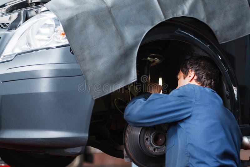 Systeem van de de autoopschorting van de reparatiemens het bevestigende bij garage royalty-vrije stock foto