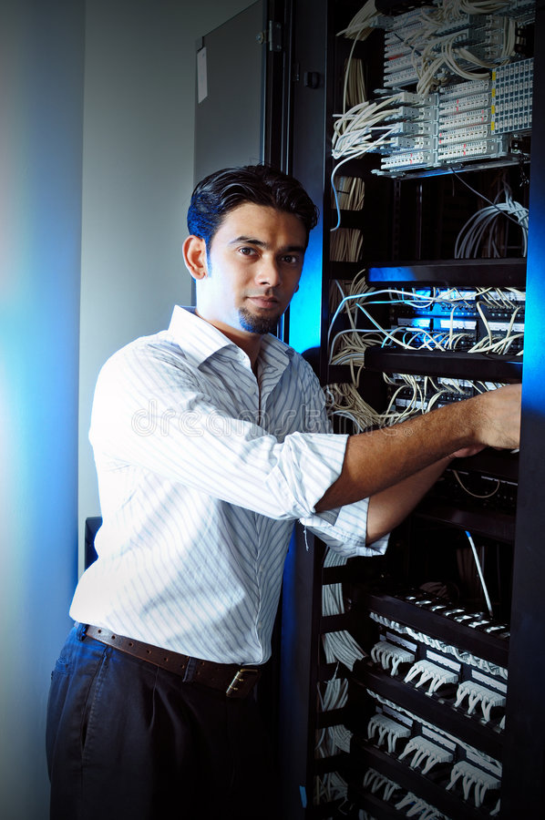 IT system administrator. Checking internet cable at server room royalty free stock photo