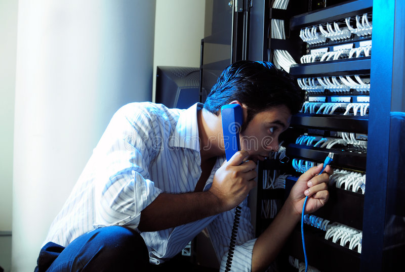 IT system administrator. Talking on the telephone while holding a internet cable at server room stock photography