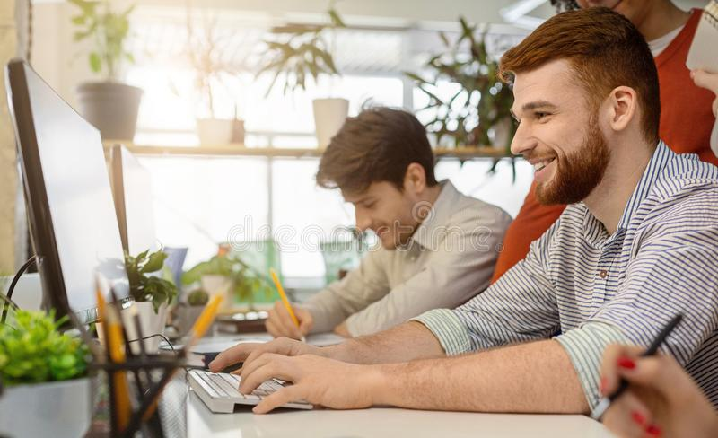 System administrator working on computer in office. Cheerful system administrator working on computer in office, upgrading software system for team, panorama stock photography