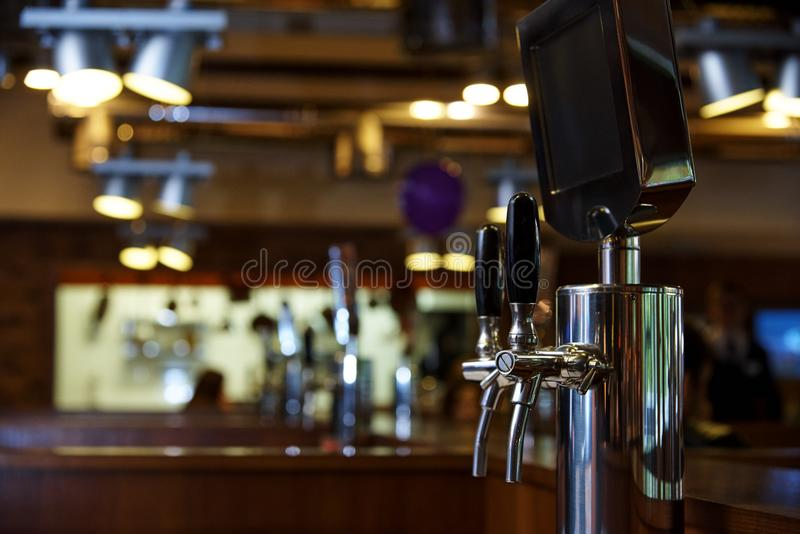 The system of bottling beer on the table of customers. On a blurred background of the bar in the brewery royalty free stock image