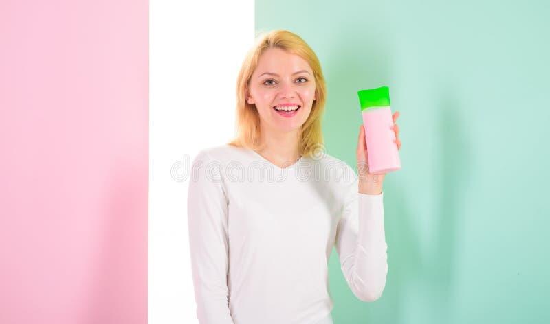 System des befeuchtenden Shampoos und des Conditioners Bedingung richtig Mädchenblondine hält Haarpflegeproduktflasche Frau lizenzfreies stockfoto