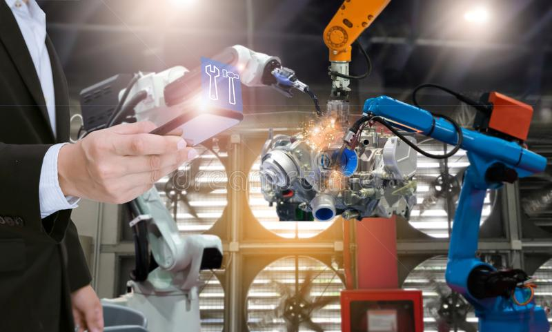 System engineer with smartphone control automation robot arms the production of factory parts engine manufacturing industry robots royalty free stock photos