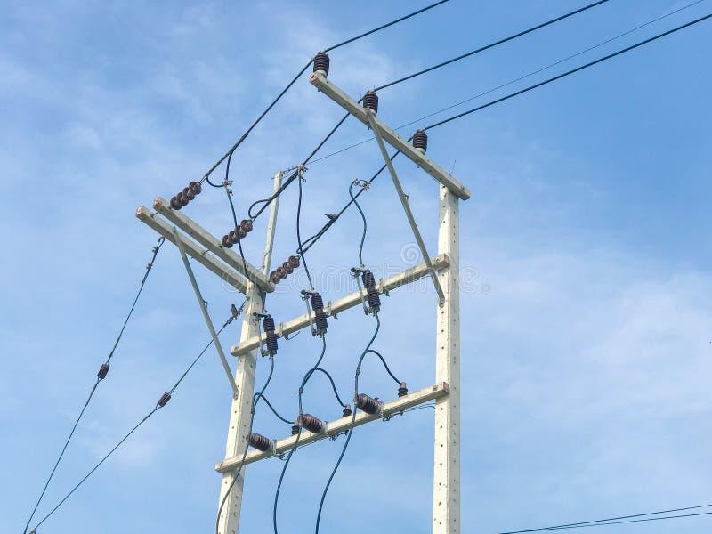 System und Drähte der Strompfostenhohen leistung mit blauem Himmel stockbilder